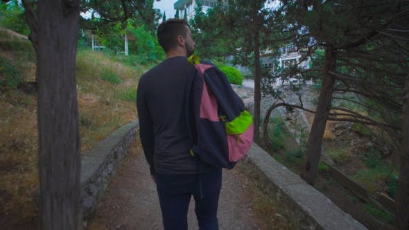 Thumbnail for Young Man Goes With a Rucksack On His Back Through The Beautiful Countryside.