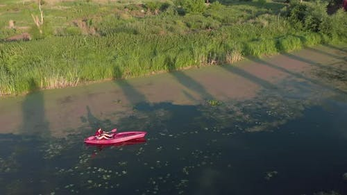 Tourist is kayaking at sunset. Girl is floating in boat on lake. Sport rowing aerial follow shot