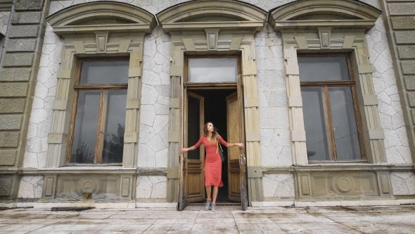 Thumbnail for Attractive Girl In Red Dress Goes On The Balcony Of An Old Manor.