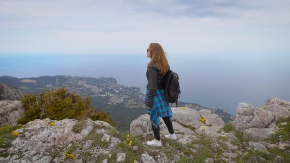 Thumbnail for Woman Traveler Looks At The Edge Of The Cliff On The Sea Bay Of Mountains In The Background
