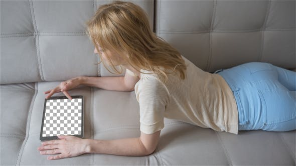 Thumbnail for Beautiful Girl Using Tablet PC with Isolated Screen Laying on Sofa at Home 1