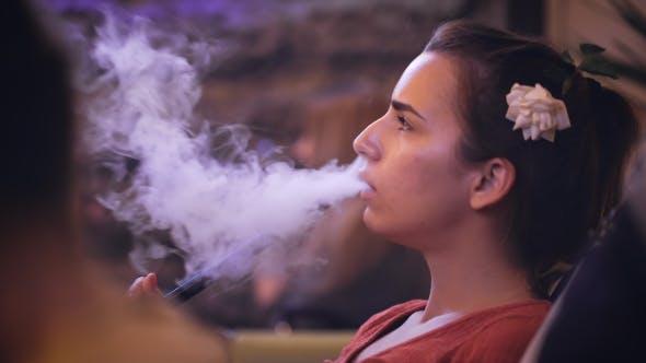 Nice Girl In a Nightclub Smokes a Hookah.