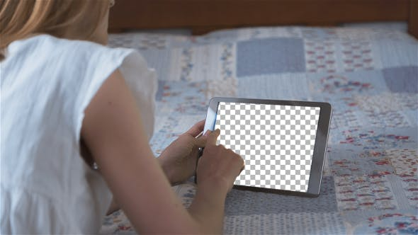 Thumbnail for Beautiful Girl Using Tablet PC with Isolated Screen Lying on Bed at Home 2