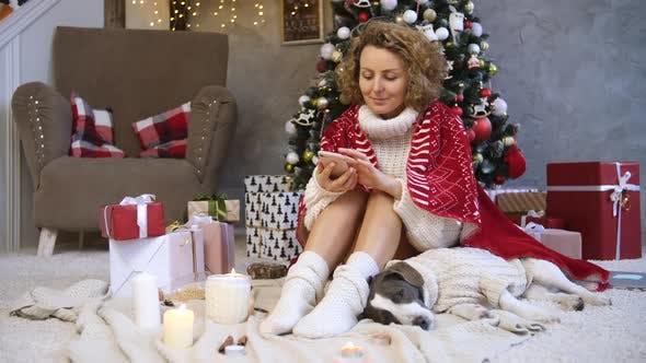 Thumbnail for Frau mit Smartphone Feiern Weihnachten mit Hund zu Hause.