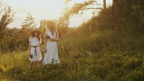 Two Girl Teenagers in White Dresses and Straw Hats with Flowers Bouquet Posing on Nature Landscape