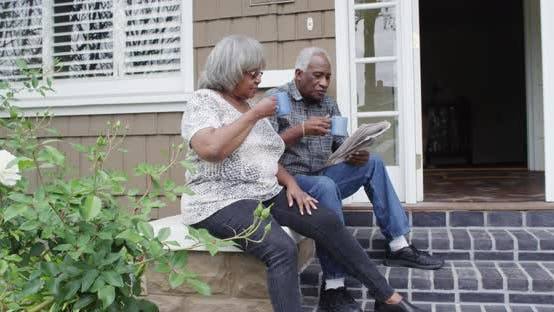 Thumbnail for Senior African couple sitting on porch reading newspaper