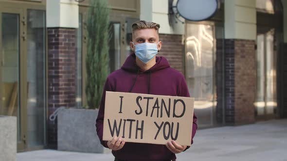 Thumbnail for Caucasian Male Protester Activist Wearing a Medical Mask Holds a Cardboard Poster with the Slogan I