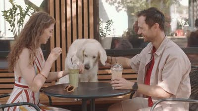 Couple Petting Dog in Cafe