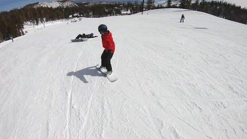 A boy snowboarder snowboarding and falling at a ski resort.