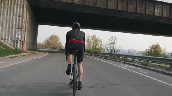 Passen Sie athletische Radfahrer, die Fahrrad unter dem Brückentraining fahren