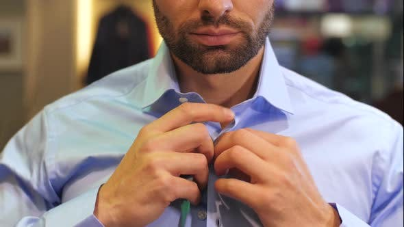 Thumbnail for Man Putting on Shirt at Wardrobe