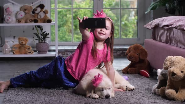 Thumbnail for Little Girl Taking Selfie Photo with Puppy at Home