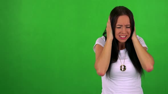 Cover Image for Young Pretty Woman Is Afraid (Woman Covers His Ears with Hands) - Green Screen - Studio