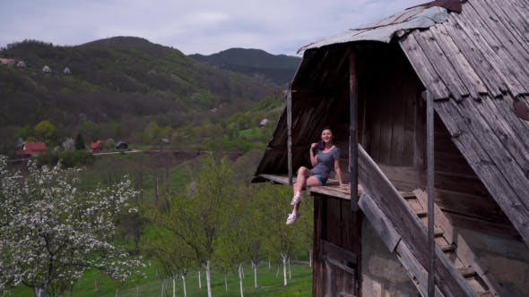 Thumbnail for Woman Sitting On Balcony Of a Wooden House, Enjoying Herself