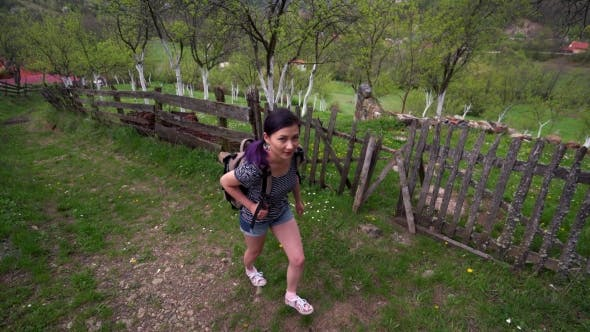 Thumbnail for Young Woman Walking On a Hill Near a Village