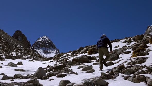 Thumbnail for Lone Hiker Clmbs Uphill On Snow Covered Rock