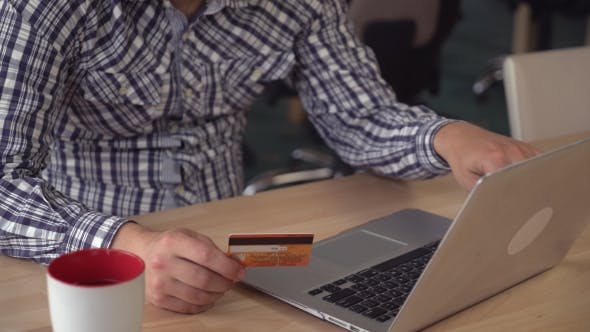 Online Banking Detail. Man Buying Via Internet Using Credit Card And Computer.