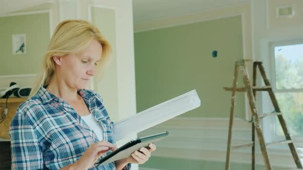 Thumbnail for A Young Female Designer Uses a Tablet in the Room of a New House Where Repairs Are Underway