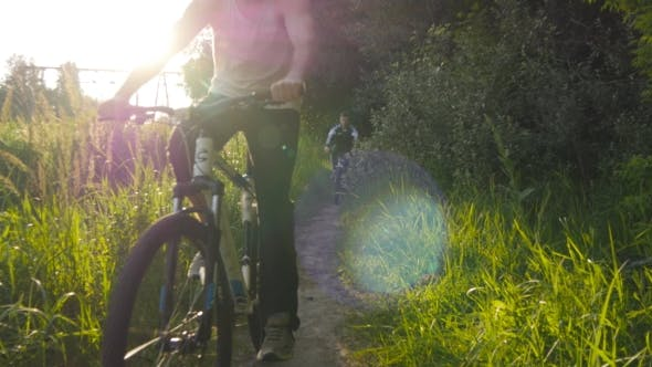 Thumbnail for Two Guy Riding Bikes Through Green Grass On The Meadow In Sunset. Friends Cycling Through a Field In
