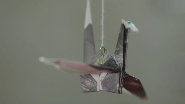 Thumbnail for Paper Origami Crane Rotating On Thread Against Gray Background