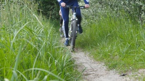 Two Guy Riding a Bike On a Forest Path.