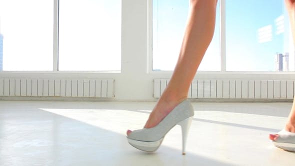 Thumbnail for Girl In High Heel Shoes Walking Against Window