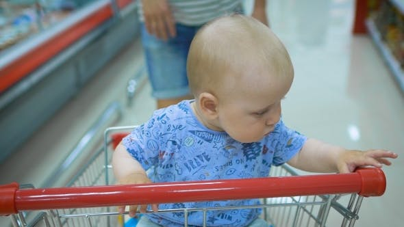 Thumbnail for Little Baby Sitting in a Grocery Cart in a Supermarket, While His Father Chooses Purchases.