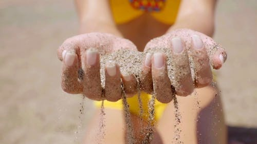 Young Woman Drizzling Sea Sand Through Her Hands
