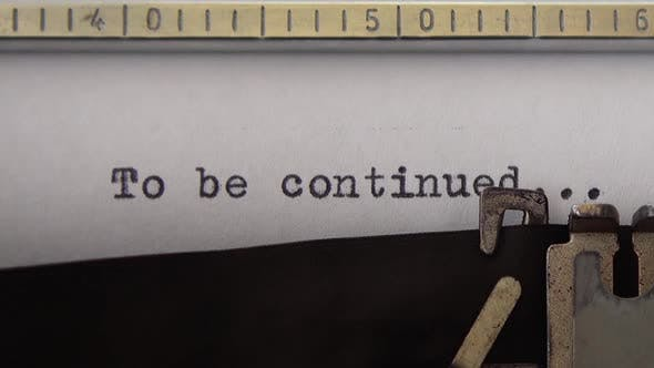 Typing phrase To be continued on retro typewriter. Close up.