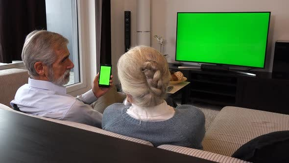 Thumbnail for Elderly Couple Sits on A Couch in A Living Room, Watches Tv with A Green Screen and Looks at Phone
