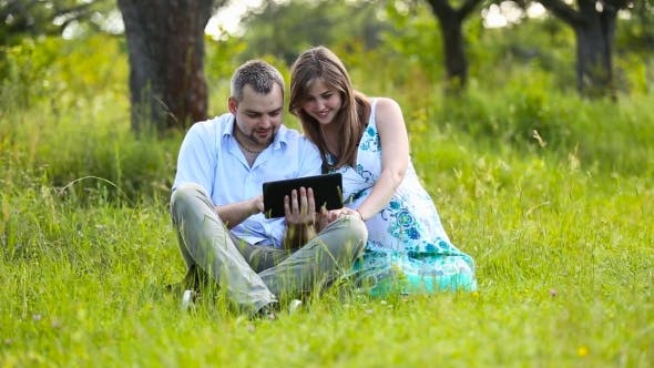 Happy Pregnant Couple With Tablet