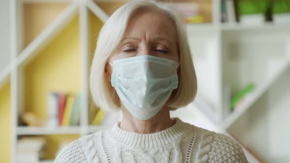 Safety and Pandemic Concept - Portrait of Senior Woman Wearing Protective Medical Mask for