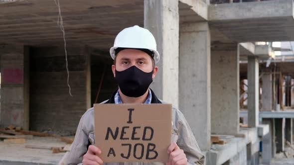 Engineer in Mask and Hardhat Shows Placard I Need a Job