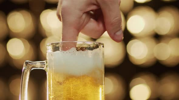 Caucasian man stirs foam with a finger in a beer mug bokeh background close-up.