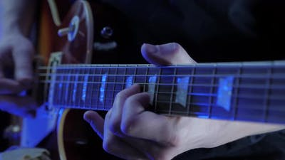 Hands playing chords on guitar strings. Music guitar online lessons. Music instruments.