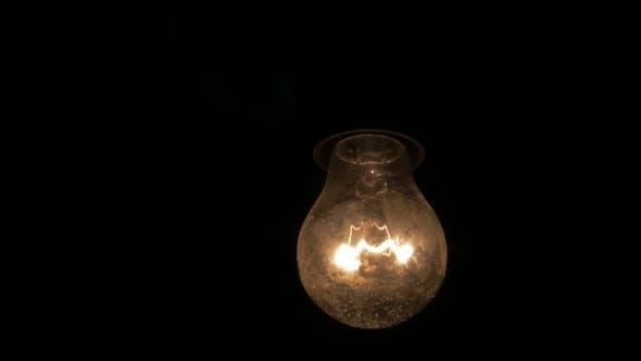Thumbnail for Slow motion dusty light bulb swings  in the dark 1920X1080 HD video - Light bulb swinging  horror sc