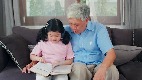 Senior Chinese, grandpa happy relax with young granddaughter girl enjoy read books and do homework.
