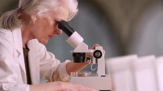 Thumbnail for Mature woman scientist or medical researcher looking at sample in microscope