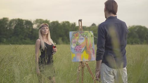 Portrait of Beautiful Blond Woman Posing for Man Drawing Picture Outdoors at Sunset. Confident Male
