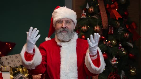 Portrait of Santa Claus Looking at the Camera and Congratulating Everyone on the Holidays