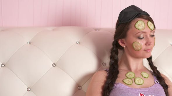 Thumbnail for Woman on Sofa with Cucumber on Her Face Reading Magazine