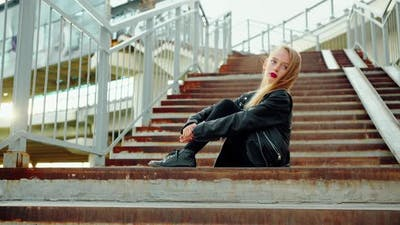 Young Fashion Model in Rock Star Look Posing on Staircase