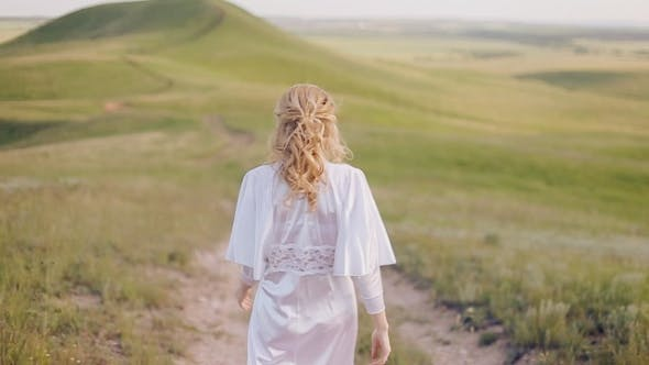 Thumbnail for Woman In White Dress Walking In The Field