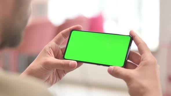 Close Up of Man Holding Smartphone with Green Chroma Screen