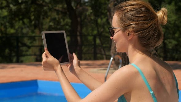 Thumbnail for Blonde In Sunglasses Is Sitting Near Swimming Pool And Communicating