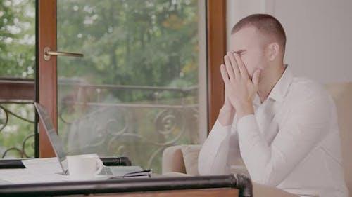 Businessman Despairing While Sitting at Laptop