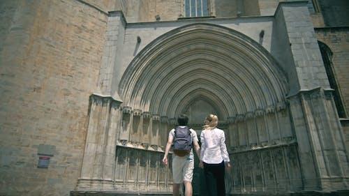 Young Tourist Couple Near Catholic Church In Girona.