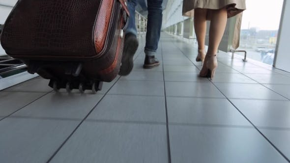 Thumbnail for Couple Of People Walks Through Airport Carrying Luggage With Them