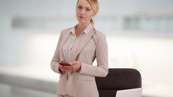 Thumbnail for Businesswoman standing at desk with smartphone