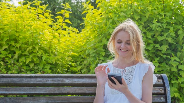 Thumbnail for Happy Smiling Girl Using a Smartphone in a City Park Sitting on a Bench 4